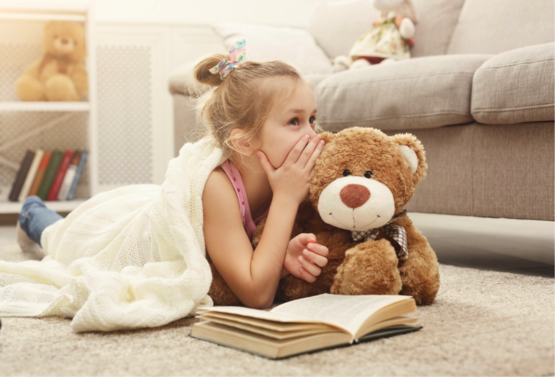 Young girl whispering to her teddy bear.