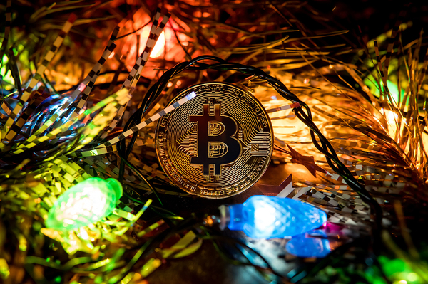 Gold coin with bitcoin symbol and holiday lights.