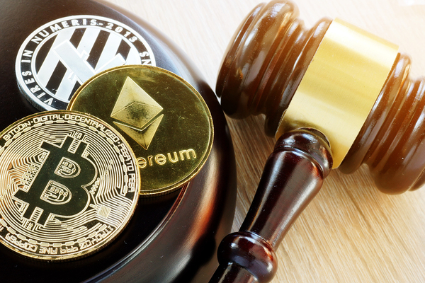 Gavel, and gold coins labeled bitcoin, ethereum and litecoin.