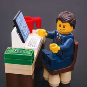 Lego man sitting at a desk.