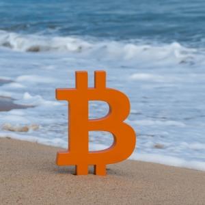 Bitcoin logo on a sandy beach.